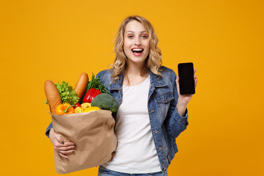 Funny girl in denim clothes isolated on orange background. Delivery service from shop or restaurant concept. Hold brown craft paper bag for takeaway with food product mobile phone with blank screen.