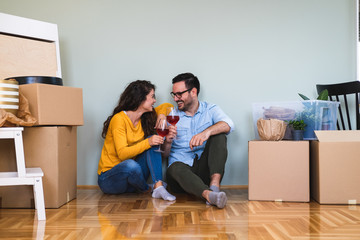 Cheers to new beginnings stock photo. Shot of a happy couple having wine to celebrate moving into new home
