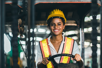 Women labor worker at forklift driver position with safety suit and helmet happy smile enjoy working in industry factory logistic shipping warehouse.