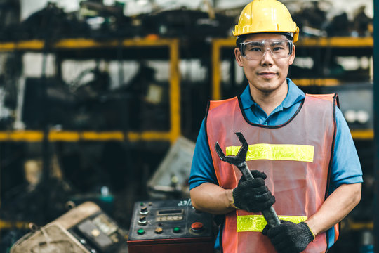 Asian Labor worker engineer with safety suit and helmet working in industry factory handle Industrial wrench.