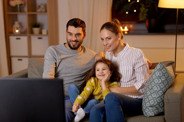 family, leisure and people concept - happy smiling father, mother and little daughter watching tv at home at night Wall mural