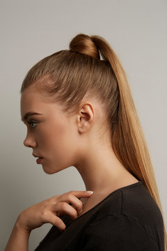 A blonde European girl with long straight hair in a high ponytail and a hair knot is posing on the gray background. The lady is wearing a black tee-shirt.