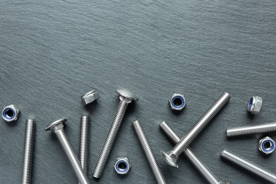 Stainless steel screws on a black texture background