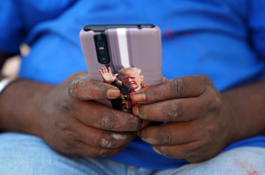 Bussa Krishna, a fan of U.S. President Donald Trump, checks his mobile phone with an image of Trump outside his house in Konney village