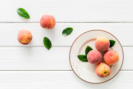 Summer fruits. Ripe red peaches on plate on white wooden table top-down copy space