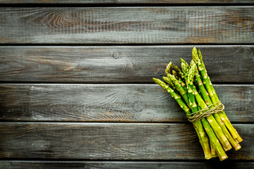 Bunch of asparagus steams on dark wooden background top-down copy space
