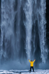 Man in the yellow jacket on the background of Skogafoss waterfall in the winter at dawn. One of the most popular places in Iceland