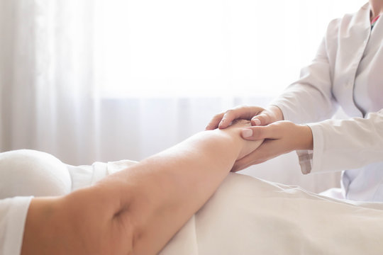 Doctor holds the hand of an elderly woman patient on a background of a window. Concept of hygienic patient care in a hospital, geriatrics, copy space