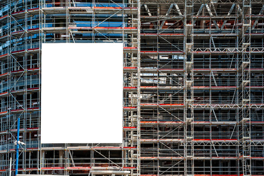 Blank white banner for advertisement hanging on the scaffolding of modern building under construction