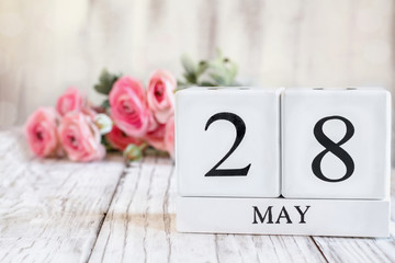 White wood calendar blocks with the date May 28 th for International Memorial Day. Selective focus with pink ranunculus in the background over a wooden table.