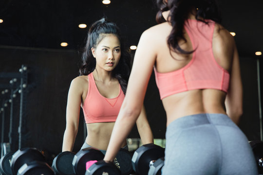 A beautiful Asian woman with a great body. Look at herself in a large mirror While holding the black dumbbell. She exercised in the gym.