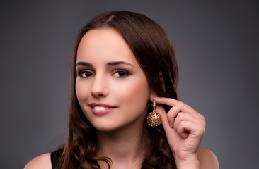 Wall Mural - Young woman showing her new earrings