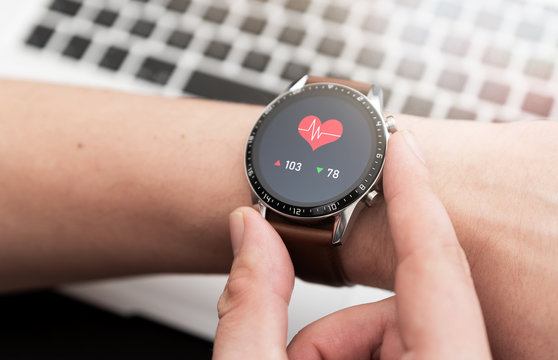 Hands with heart icon on smartwatch