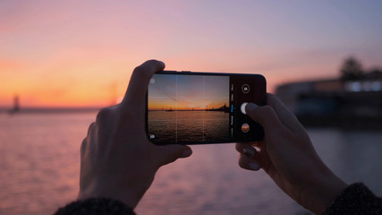 Close-up of a woman's hands with a phone taking photos of a bright sunset and the sea.
