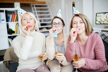 Portrait of three happy women blowing party horns and looking at camera while celebrating birthday at home