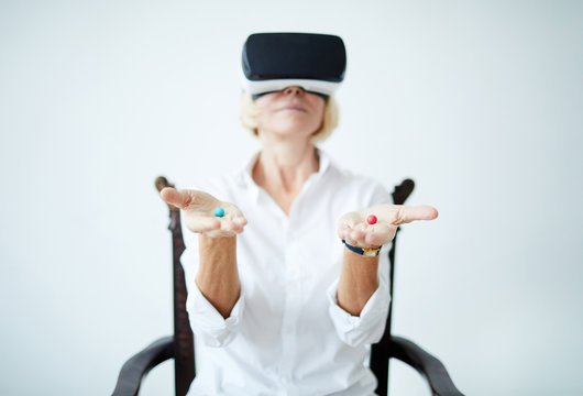 Portrait of mature woman wearing VR headset and holding two different pills in hands, focus on foreground