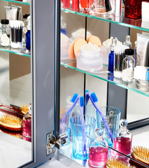 Open mirrored medicine cabinet with toiletries on shelves