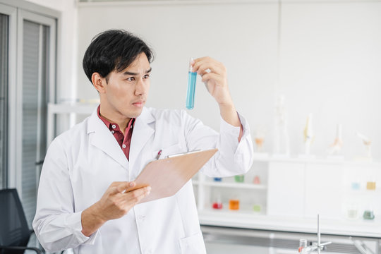 A male asian scientist holding a test tube with blue solution in one hand and clipboard in another in a laboratory setting.