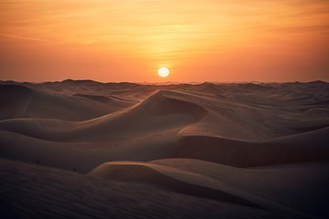 Sand dunes in desert landscape at sunset