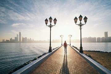 Man walking on sidewalk against urban skyline at sunrise
