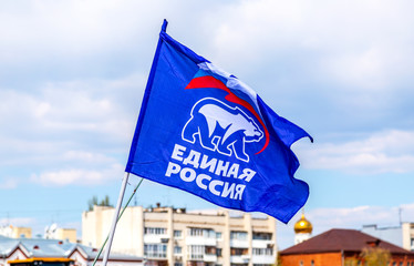 Flag of the party United Russia against the blue sky