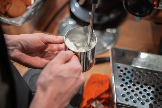 The Barista whips milk on a professional coffee machine.