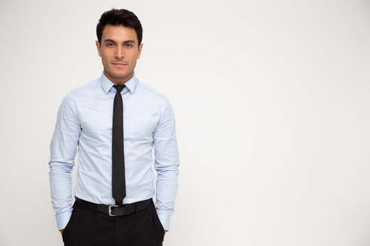 Young businessman standing with hands in pocket isolated over white background