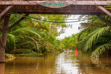 Beautiful view of people in the boats in a river surrounded by lush nature in Cambodia Wall mural