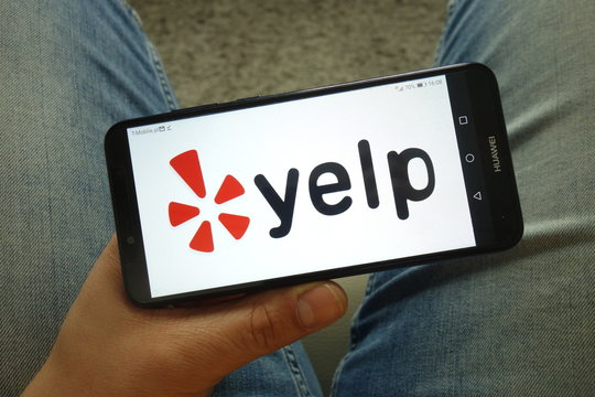 KONSKIE, POLAND - May 04, 2019: Man holding smartphone with Yelp service logo