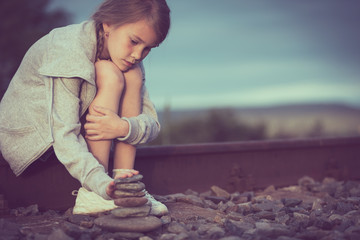 Portrait of young sad girl sitting outdoors  on the railway