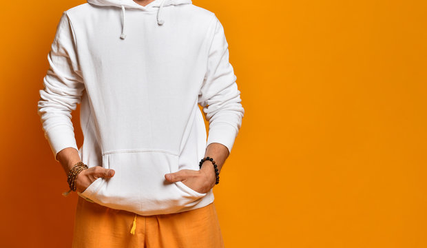 man in a white sweatshirt, pants and bracelets. Folded hands in pockets and posing on an orange background. Fashion and Style. Close copy space