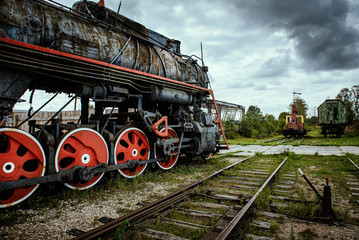 Old steam train locomotive with dramatic cloud background.