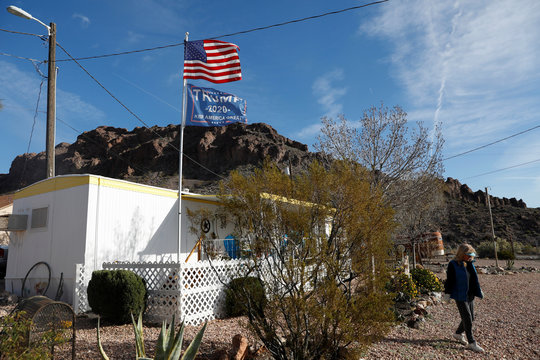 A U.S. flag and another supporting U.S. President Donald Trump fly from a woman's trailer home in Searchlight, Nevada