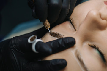 Hands in black gloves hold the manipulator with the microblading needle and draw her hair on the girl's eyebrows close-up.