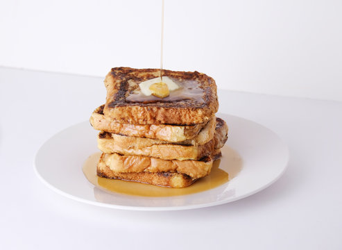 Stack of french toast bread with butter and syrup for breakfast food on white background.