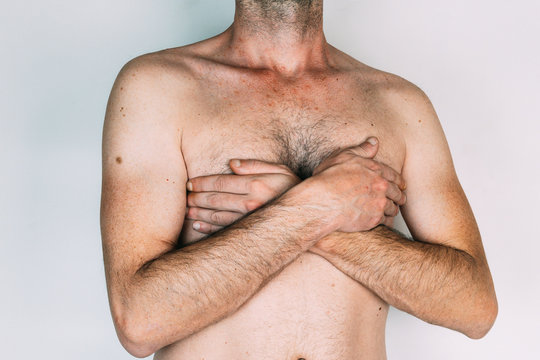 Caucasian man without shirt with hands on chest, isolated on gray background