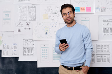 Horizontal medium portrait shot of young Caucasian man working in IT industry standing with smartphone looking at camera