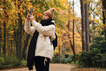 Attractive girl walking through beautiful autumn park and taking photos on cellphone