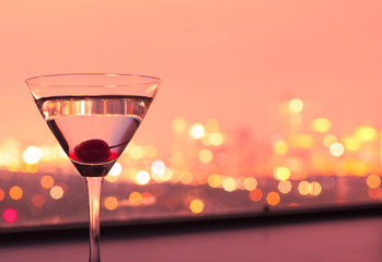 Wall Mural - Martini glass against city sunset.