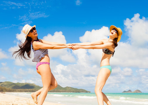 Young teen girls having fun playing laughing on a beautiful beach. People spring break, and summer fun concept.