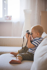 Cute boy is playing with a vintage camera while sitting on a sofa. A child examines the camera trying to find out how it works. Early development for children. Toning and artificial noise