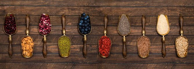 Various superfoods in vintage scoops pomegranate seeds, almond, blueberries, mung bean dry goji, chia, sesame, flax, seeds and lantils. Vegan, vegetarian healthy eating diet organic products concept.