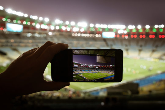 Smartphone photographing football game on the stadium