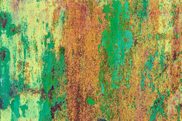 Part of old metal exterior doors. Yellow and green painted, in bouncing layers,  rusty surface with...