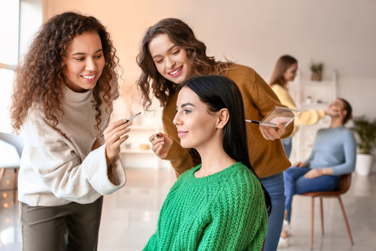 Young woman teaching student in makeup school