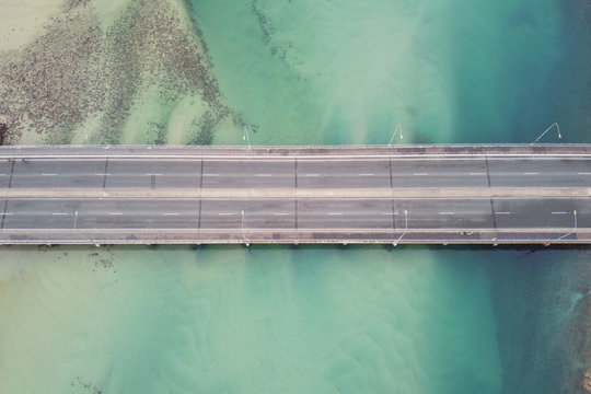Aerial top view of close up bridge over green ocean coastline, top view drone shot, transportation, industrial and reopening tourism concept