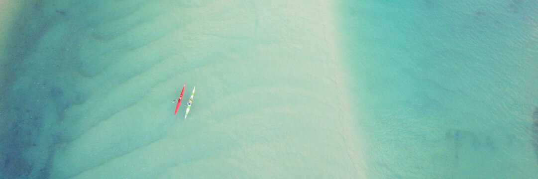 Aerial top view of couple people kayaking over  blue  creek ocean, drone shot for holidays destination, peaceful retreat relaxation, decarbonisation concept, World Oceans Day, reopen tourism