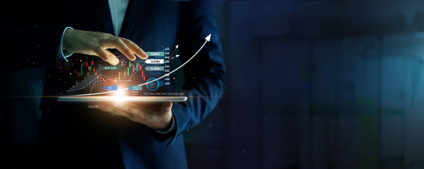Businessman holding tablet and analysis stock market, currency exchange and banking, showing a growing virtual hologram of statistics, graph and chart, Business growth, planing and strategy  concept. Fotomurales