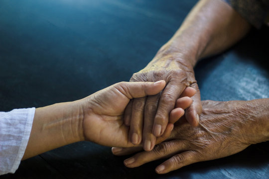 Daughter holding hand of mother elderly that is alzheimer and parkinson patient on dark background.