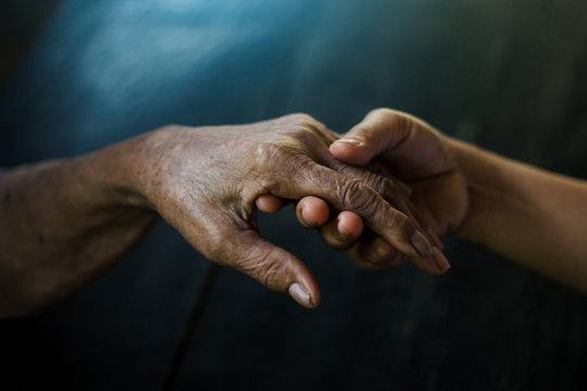 Daughter holding hand of mother elderly that is alzheimer and parkinson patient on dark background.